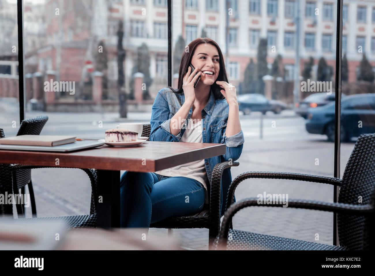 Allegro freelancer avente piacevole conversazione telefonica Immagini Stock