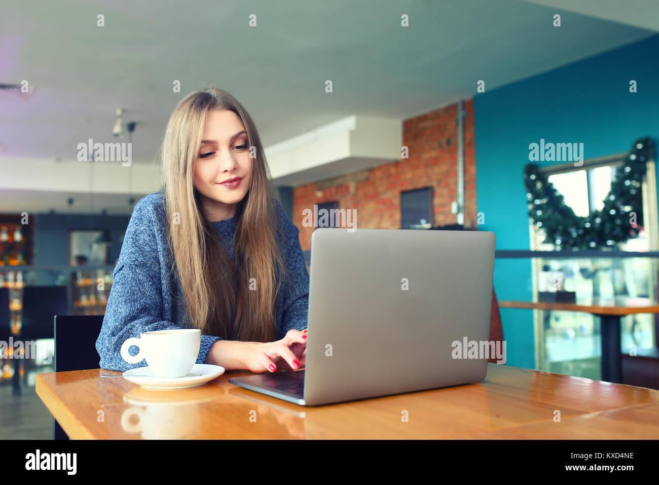 Donna al lavoro su computer portatile in una caffetteria. Giovane donna seduta al tavolo di un caffè usinglaptop. Immagini Stock