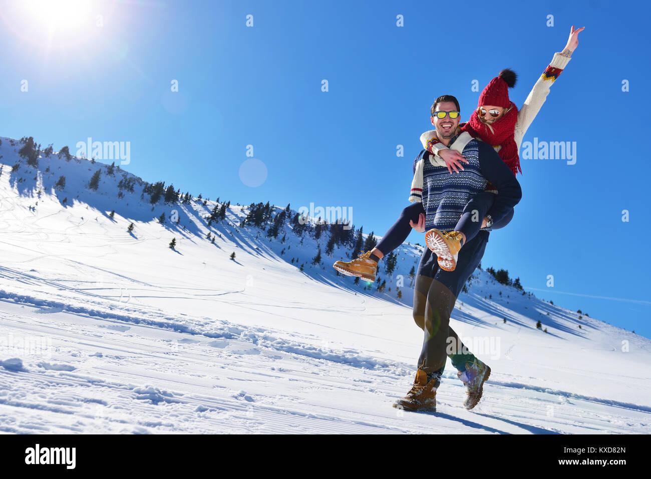 Coppia giovane divertirsi sulla neve. Felice l'uomo alla montagna dando piggyback ride per la sua ragazza sorridente. Immagini Stock