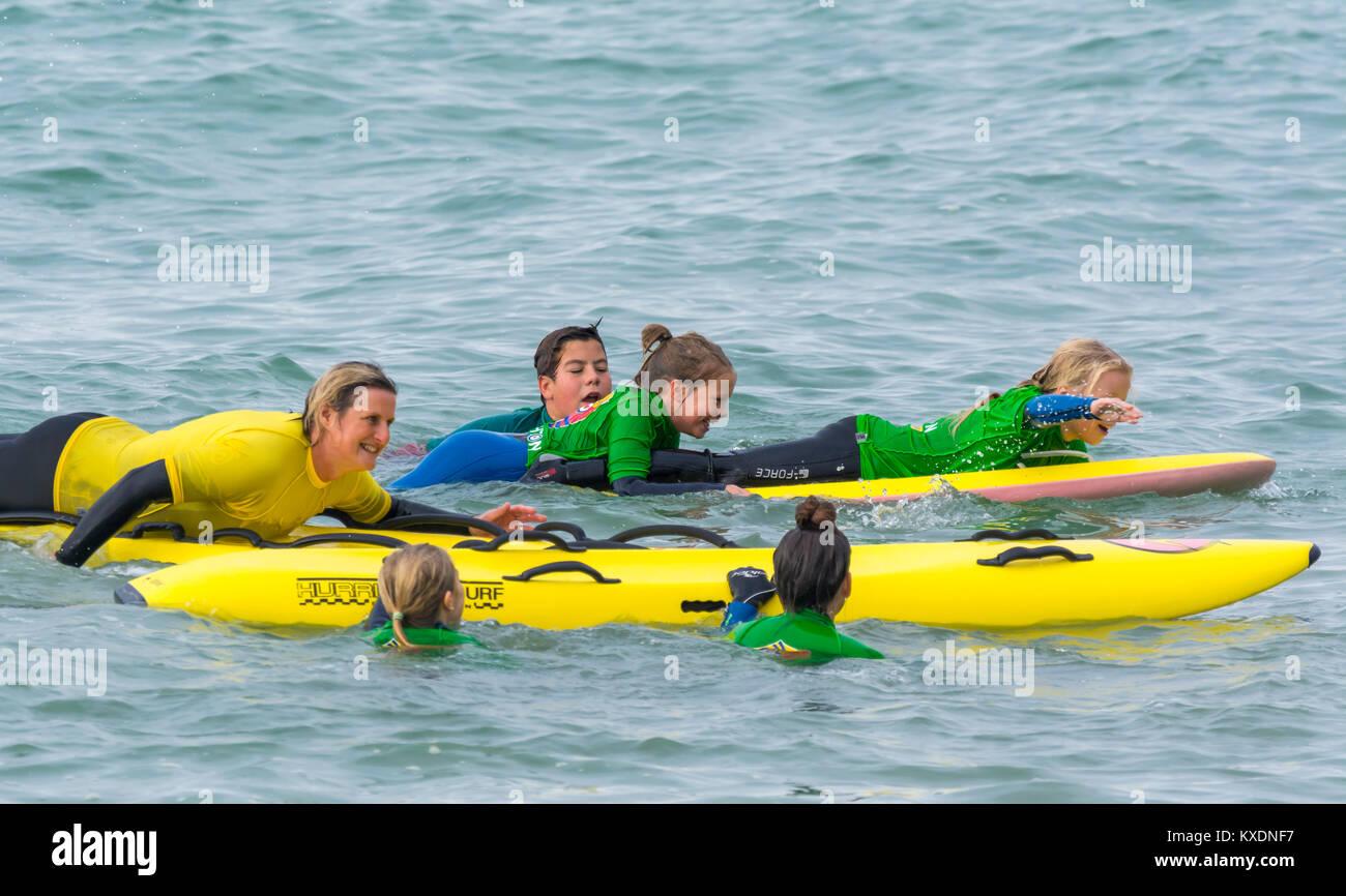 La donna la formazione di giovani bambini e ragazzi come utilizzare un paddleboard in mare nel Regno Unito. Immagini Stock