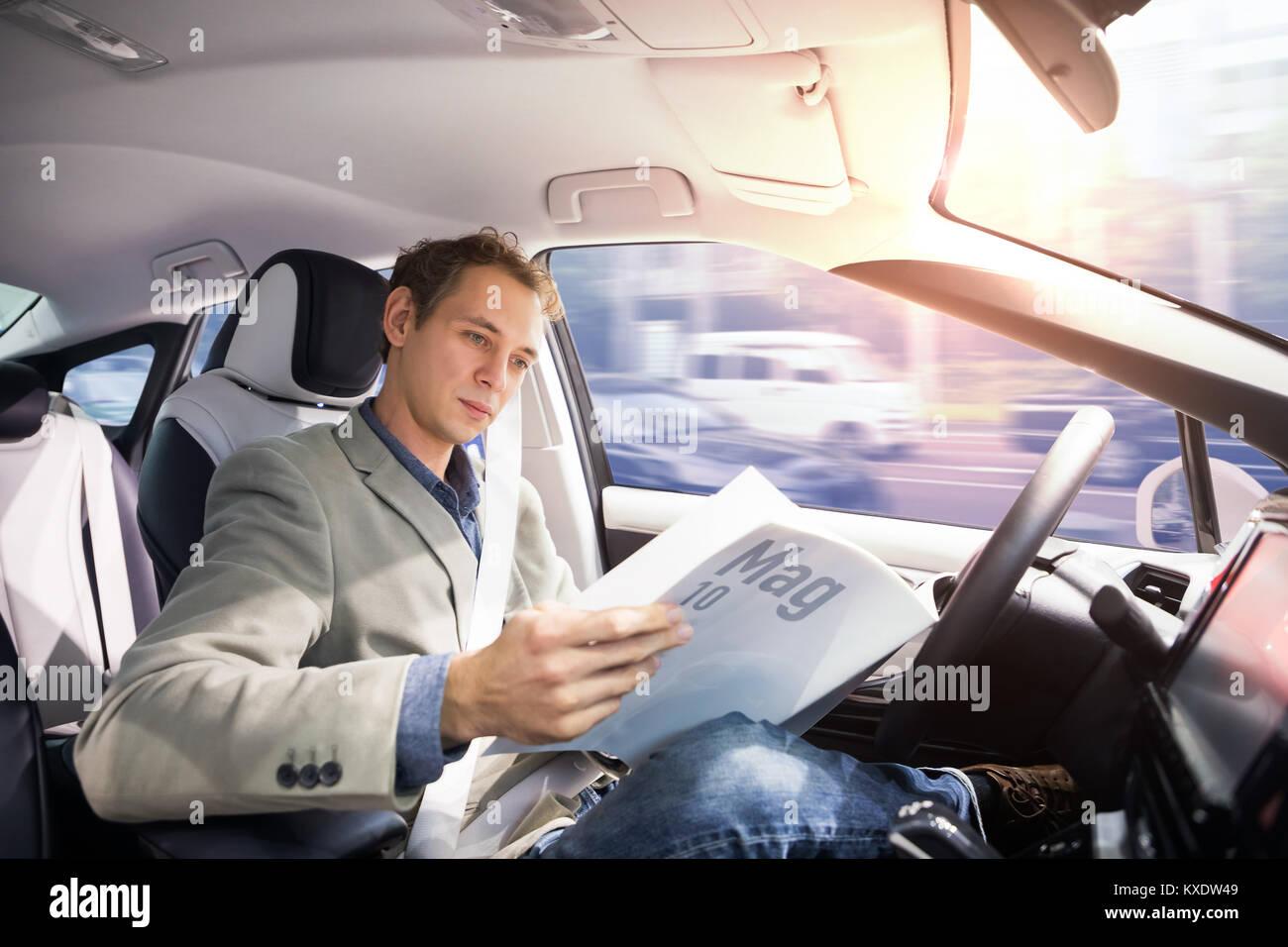 Driver caucasica rivista di lettura in auto autonoma. Auto durante la guida del veicolo. Driverless car. Foto Stock