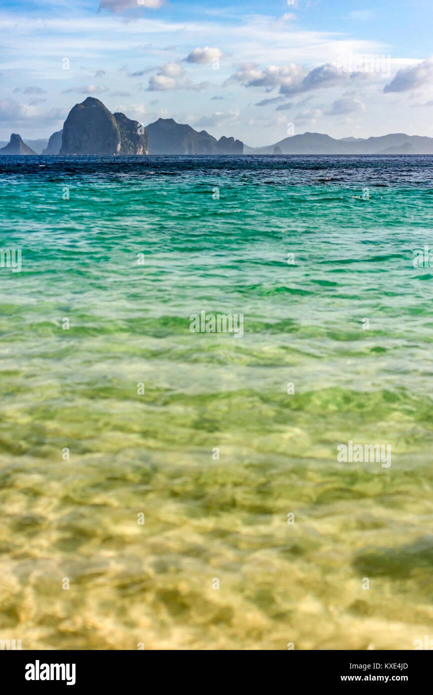 Piccole isole sat all'orizzonte prese a basso angolo su un vuoto calmo mare tropicale con profondità di Immagini Stock