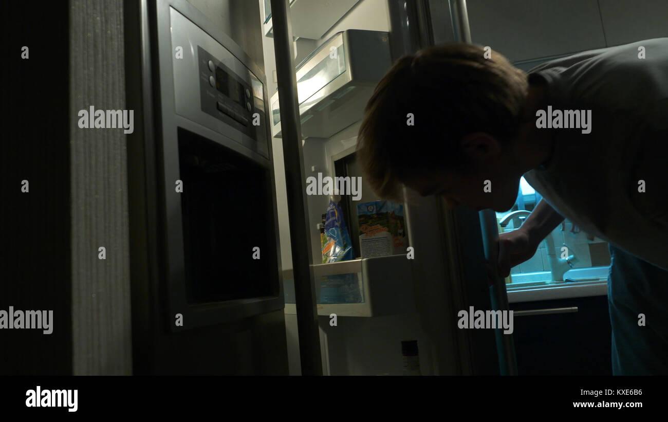 Ritratto di un uomo prendendo il cibo dal frigorifero. Ritratto di un uomo affamato in cerca di cibo in frigorifero. Immagini Stock