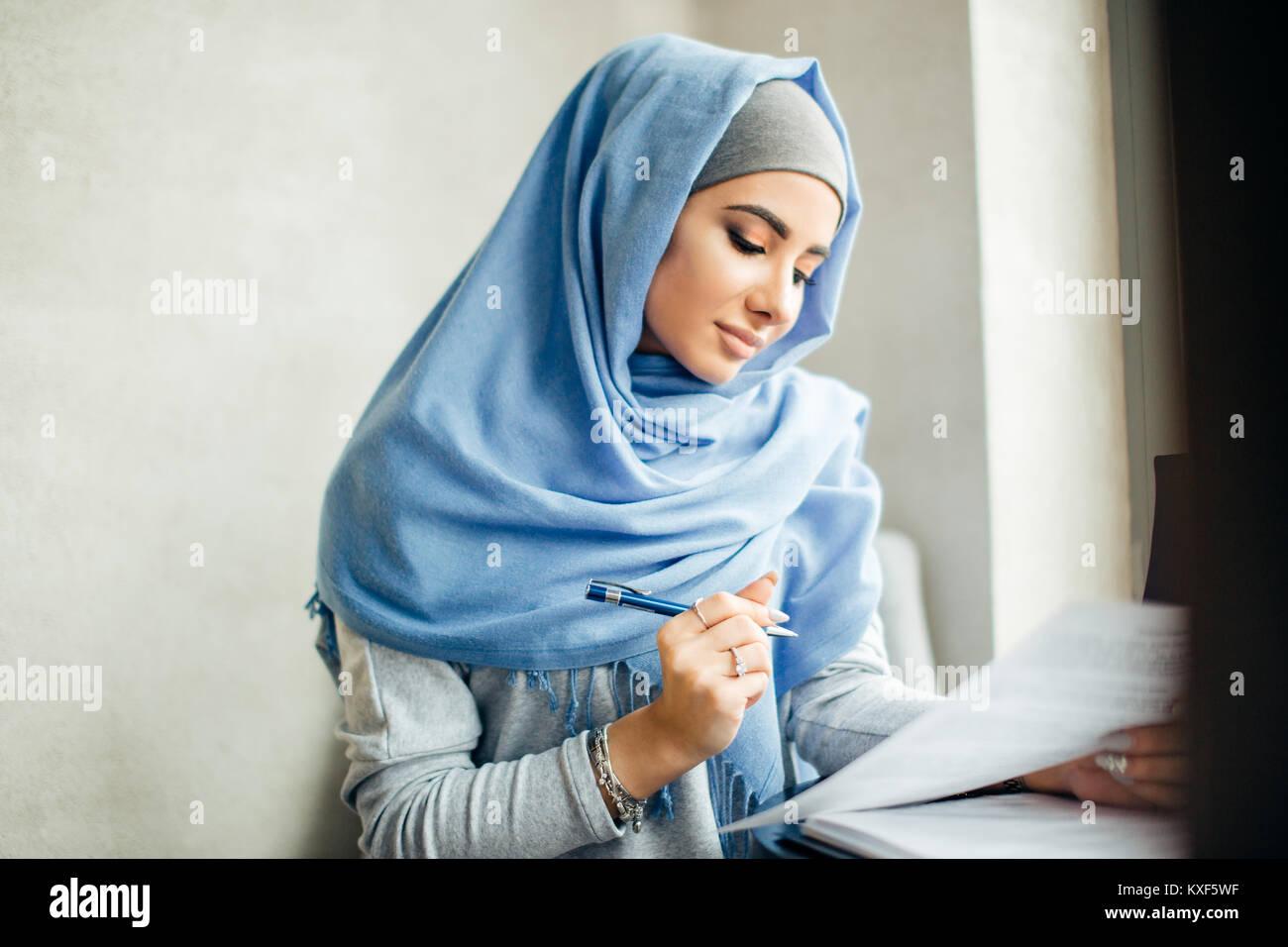 Bella donna musulmana di lavoro con documenti. business, il concetto di stile di vita Immagini Stock