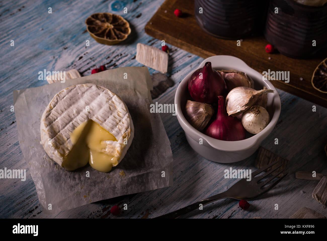 La foto in orizzontale del fuso a caldo di formaggio camembert sul foglio di carta con ciotola piena di aglio e Immagini Stock