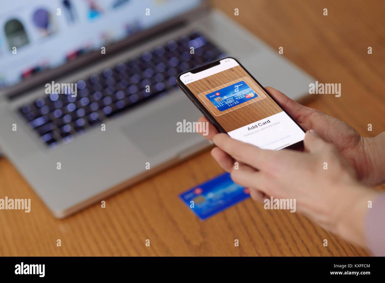 Donna con iPhone X nella sua mano la scansione di una carta di credito con Apple paga, Apple portafogli elettronici di pagamento app Foto Stock