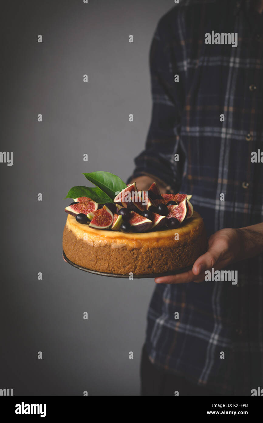 Tenendo la cheesecake in mani. In casa la cheesecake con frutti nelle mani di sesso maschile. Messa a fuoco selettiva Immagini Stock