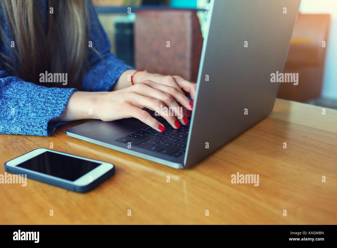 Close up le mani delle donne. Donna al lavoro su computer portatile in una caffetteria. Giovane donna seduta al Immagini Stock