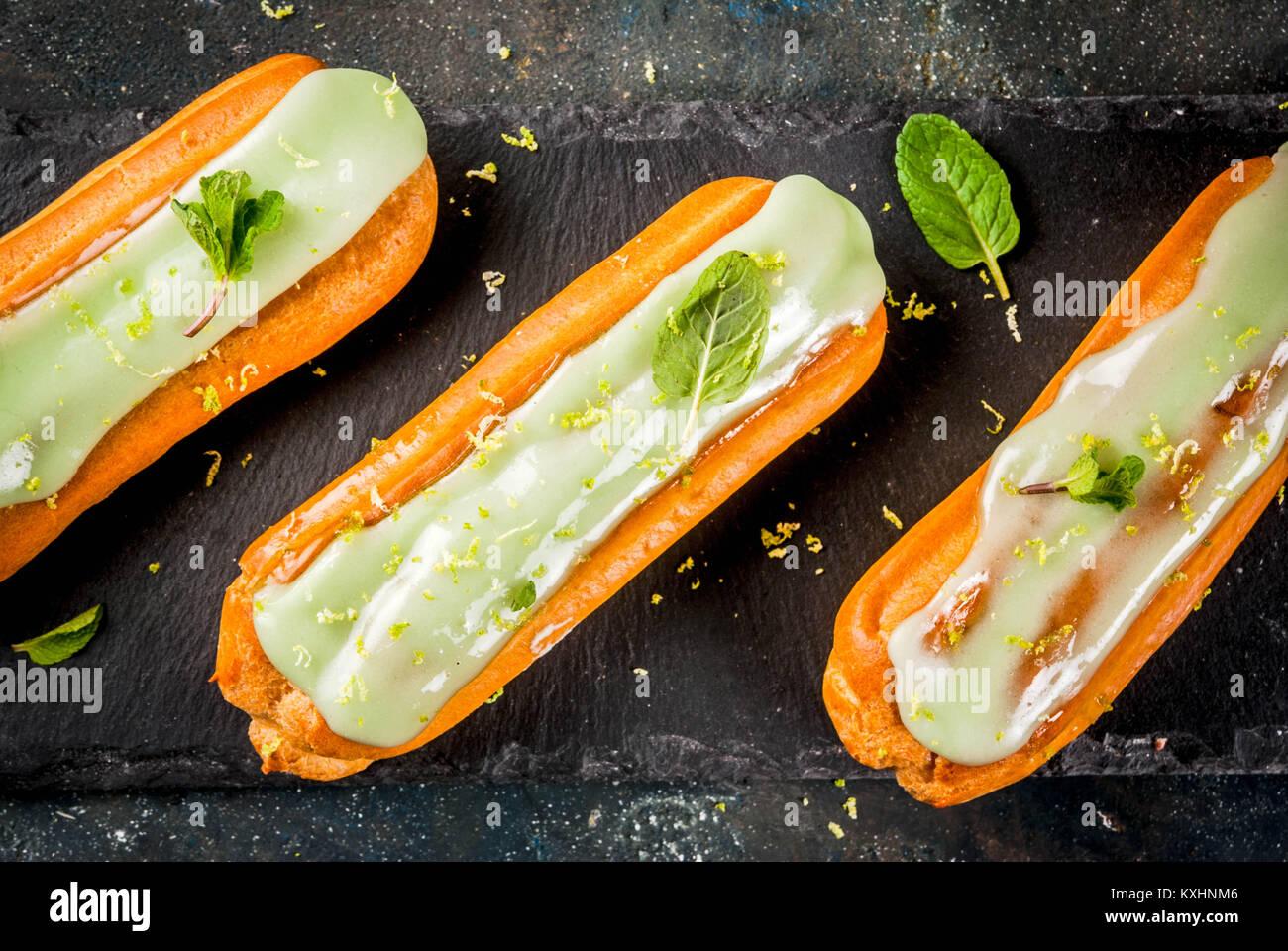 Tradizionale Francese dessert. Il Mojito Eclairs con la scorza del lime e foglie di menta, su sfondo blu scuro, Immagini Stock
