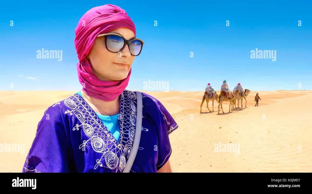 Ritratto di donna bella in arabo abbigliamento tradizionale sullo sfondo di turisti a cavallo di cammelli. Deserto Immagini Stock