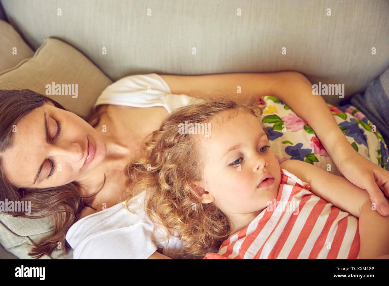 Donna incinta e la figlia sdraiata su un divano Immagini Stock