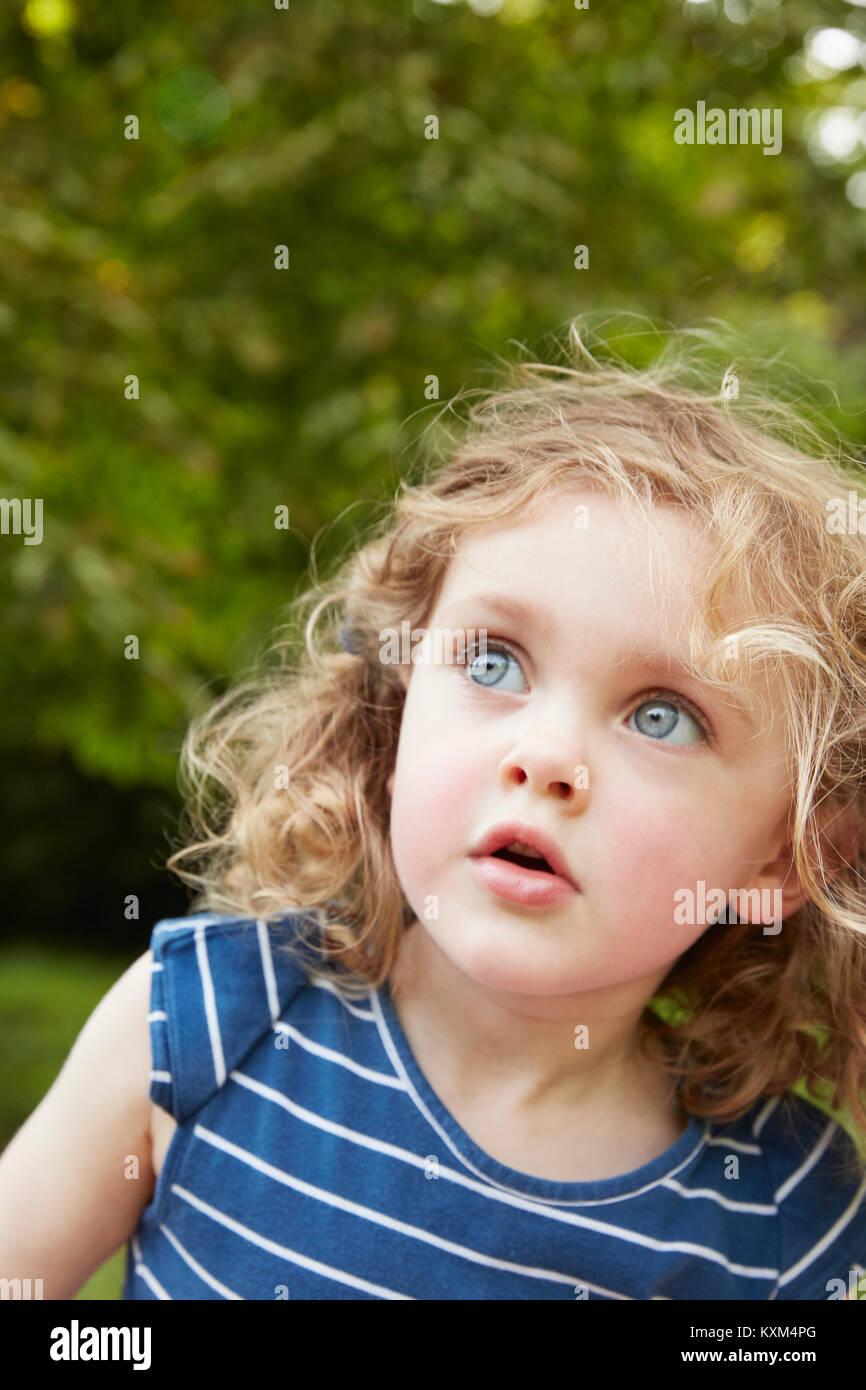 Ritratto di biondi capelli ondulati ragazza con gli occhi blu guardando in posizione di parcheggio Foto Stock
