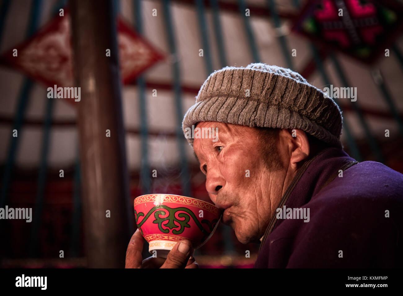Rural vecchio uomo mongolo aquila kazaka hunter sorseggiando bere il tè all'interno di ger Immagini Stock