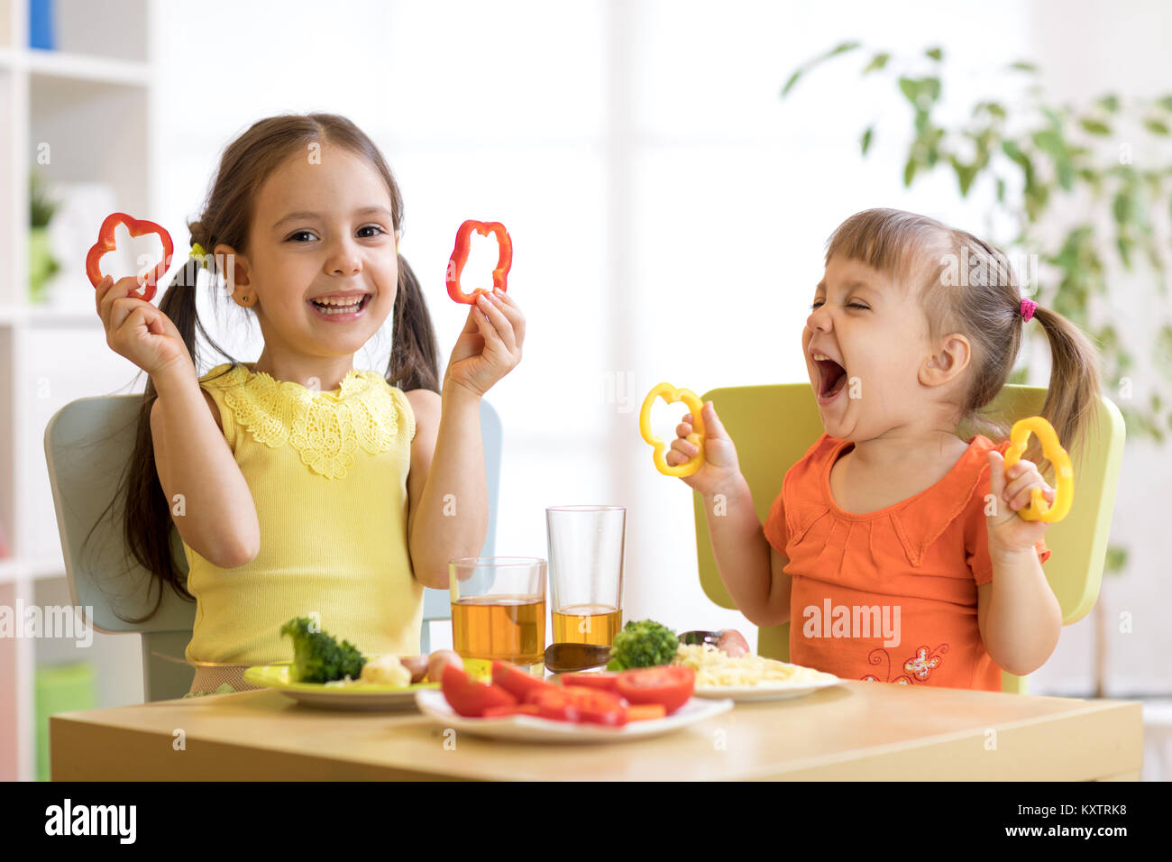 Funny bambini allegri ragazze mangiare cibo sano. Pranzo bimbi a casa o asilo nido. Immagini Stock