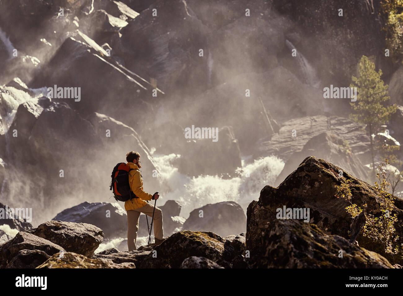 Escursionista escursionismo con zaino guardando la cascata nel parco in bella estate natura paesaggio. Ritratto Immagini Stock