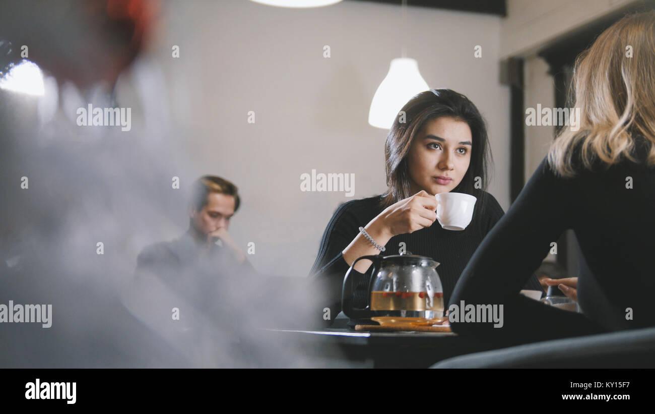 Piuttosto giovane donna a bere caffè e sorridente nel cafe Immagini Stock