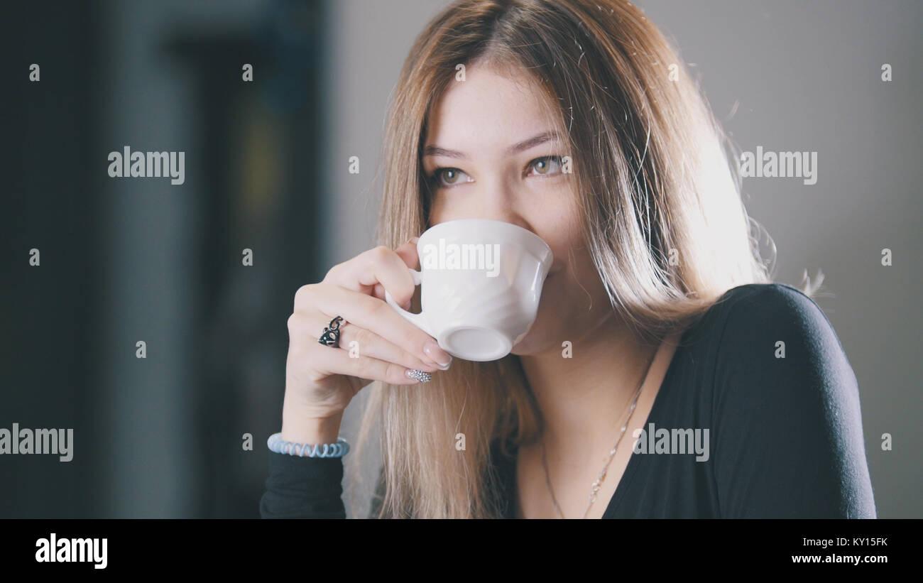 Bella ragazza bionda a bere caffè e sorridente nel cafe Immagini Stock
