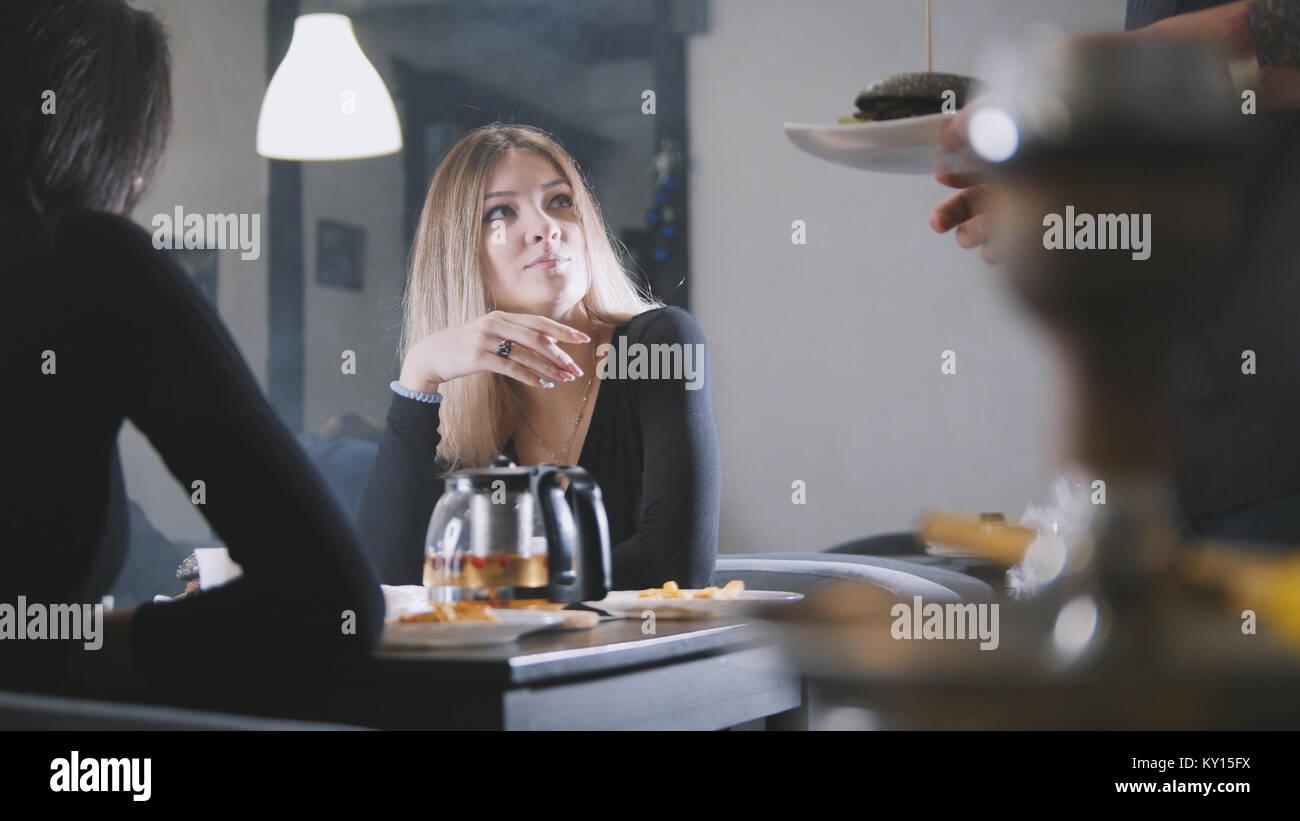 Giovani donne amici parlano in cafe, il cameriere ti porta burger Immagini Stock