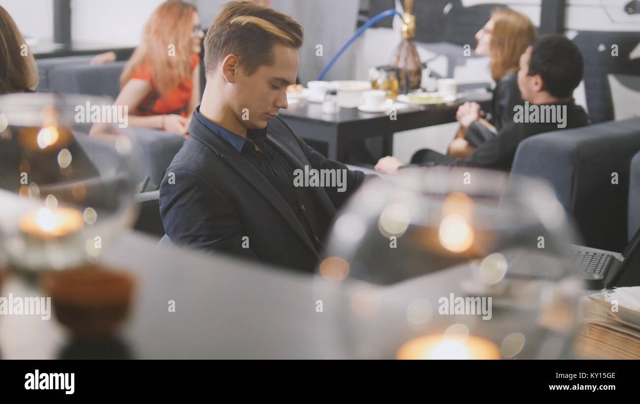 Uomo seduto nella caffetteria con caffè Immagini Stock