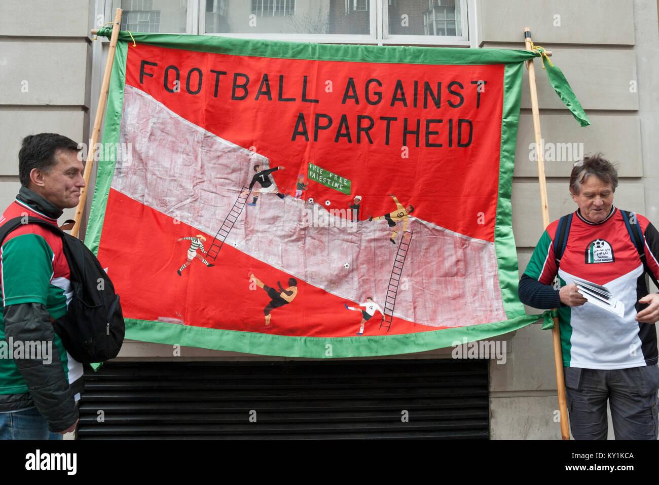 Due manifestanti che indossa la Palestina solidarietà con i colori large banner 'Calcio contro l apartheid'showing Immagini Stock