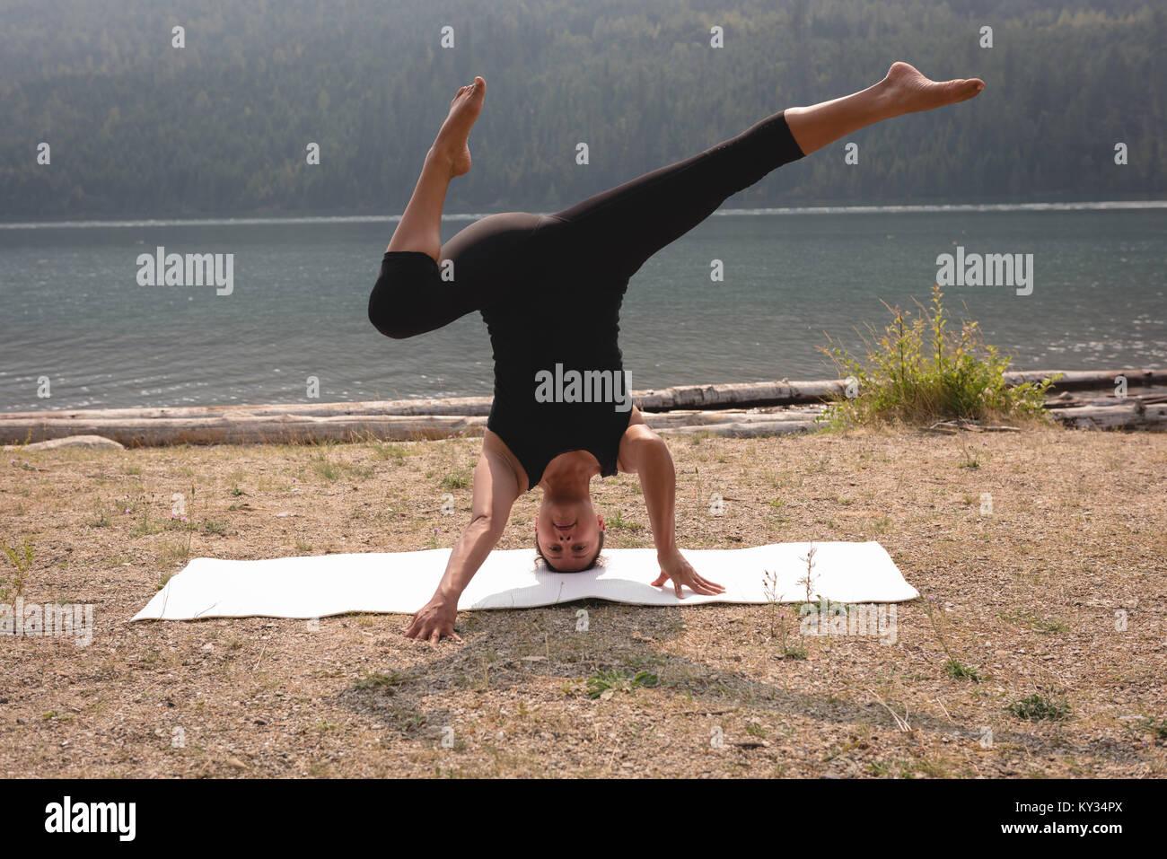 Sportivo da donna pratica testa supporto vicino alla costa del mare Immagini Stock