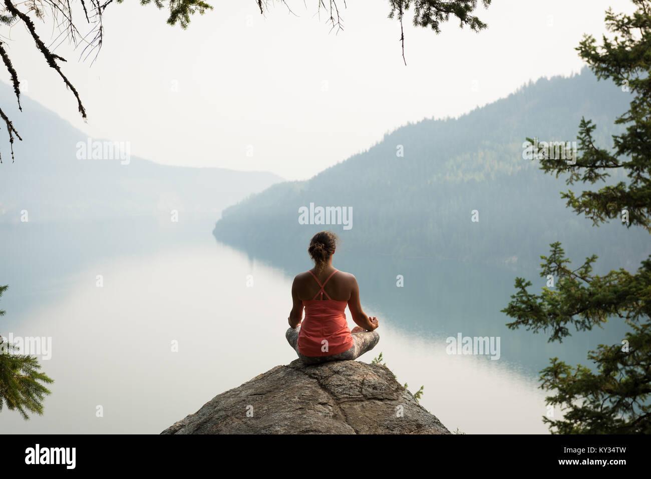 Montare donna seduta nella postura meditando sul bordo di una roccia Immagini Stock