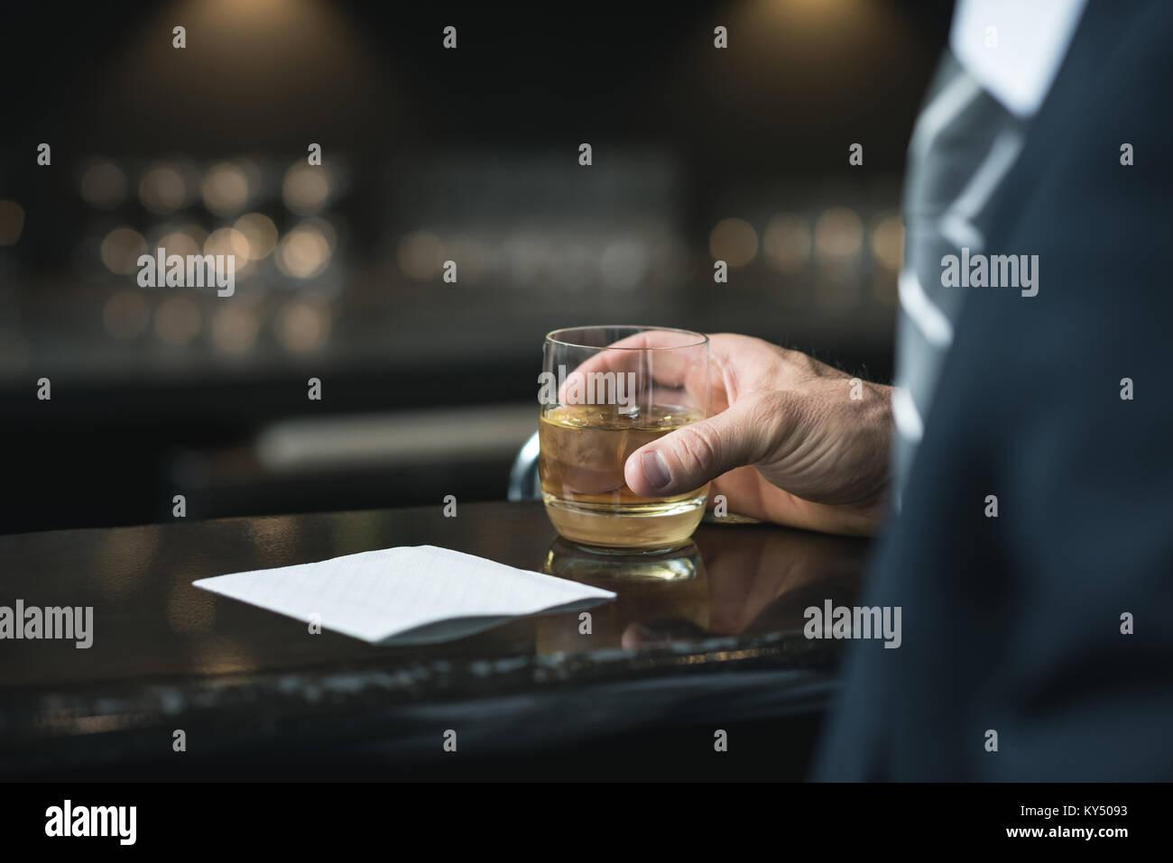 La sezione centrale di imprenditore avente un bicchiere di whisky Immagini Stock