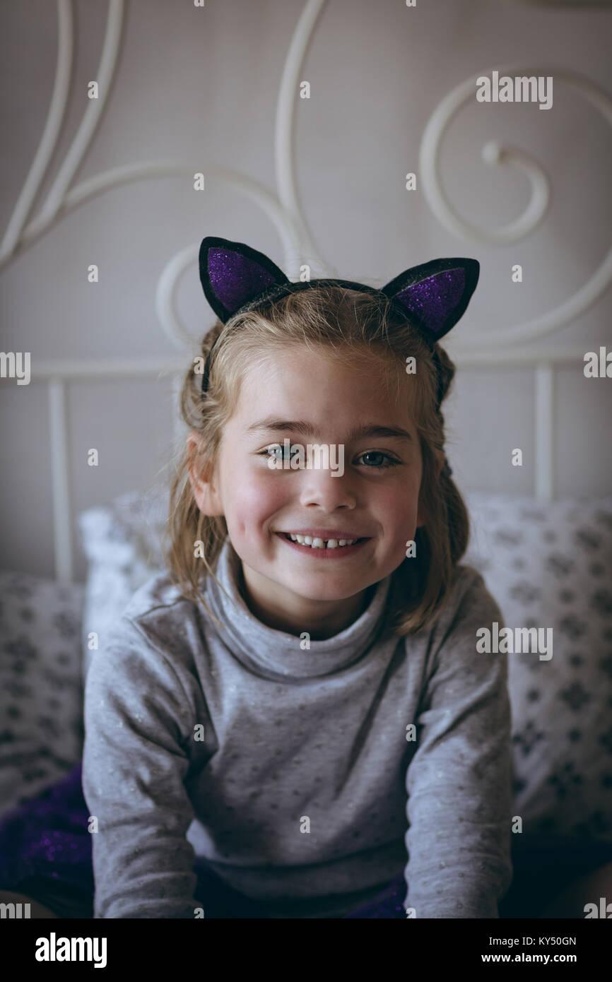 Ritratto di sorridente ragazza seduta sul letto Foto Stock