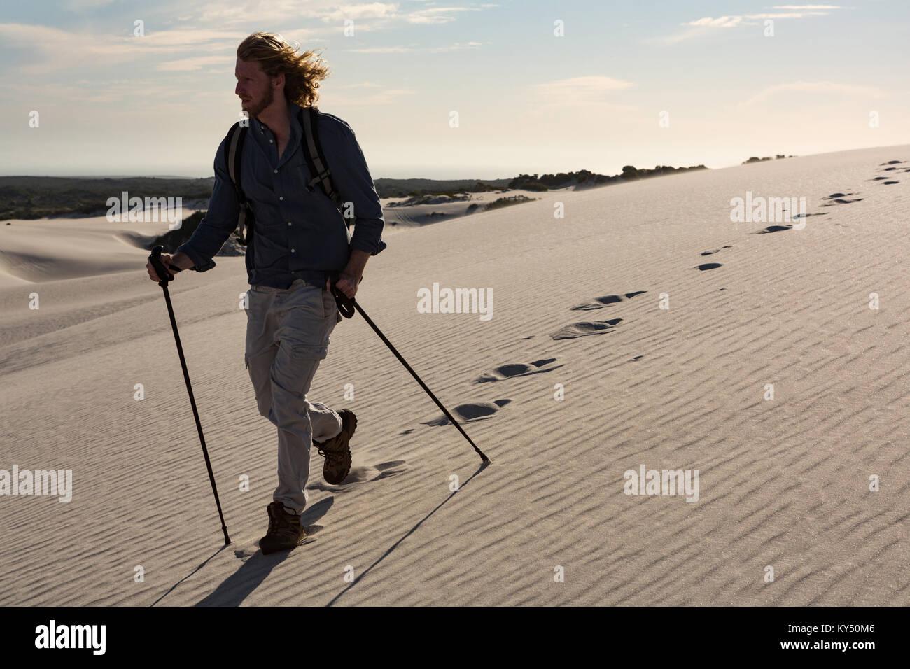 Escursionista con polo trekking a piedi sulla sabbia Immagini Stock