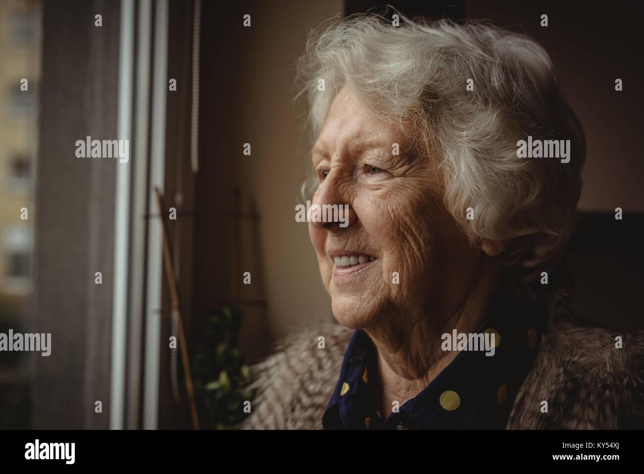 Sorridente donna senior guardando fuori della finestra Immagini Stock