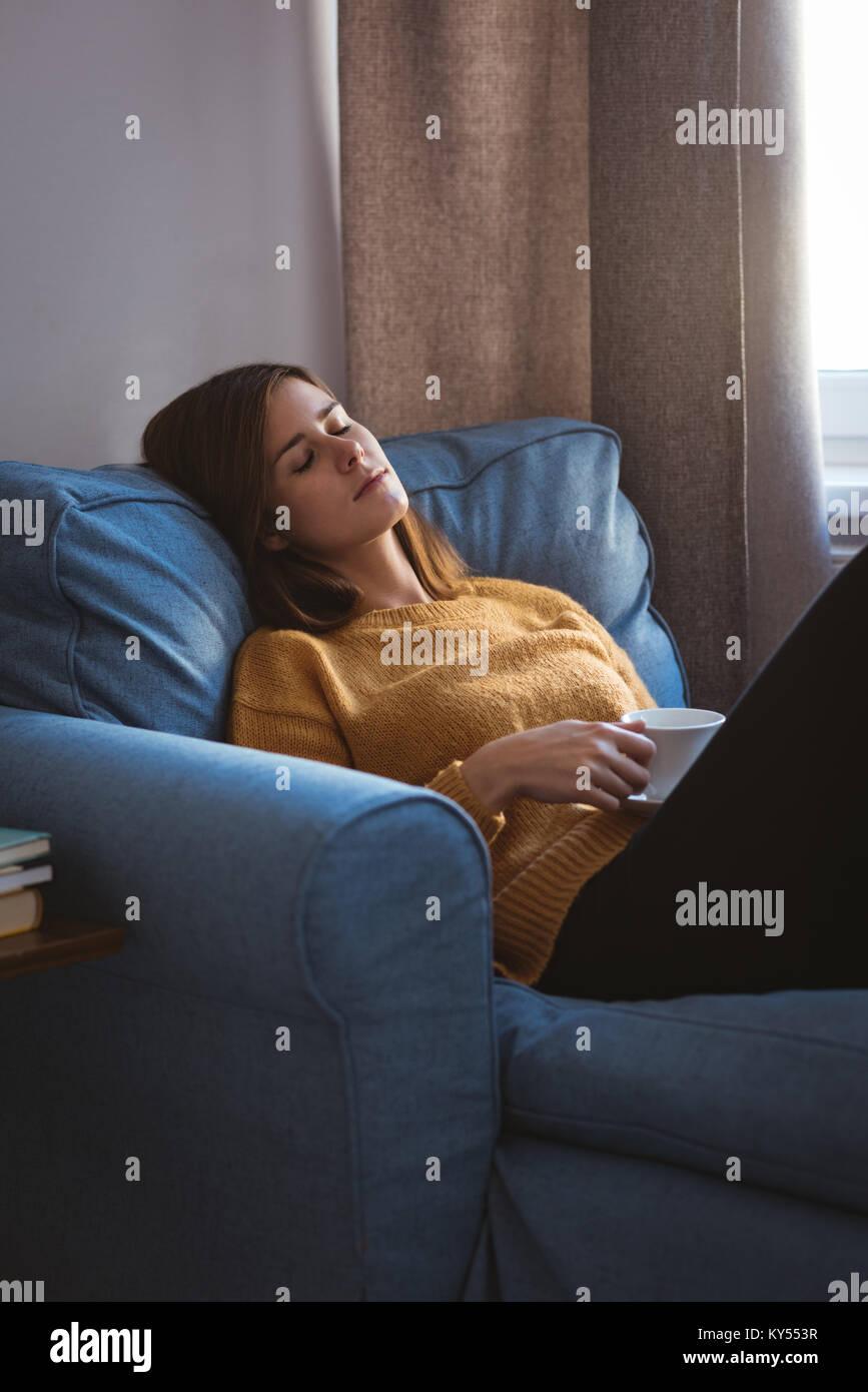 Giovane donna rilassante sul divano tenendo una tazza di caffè nella stanza vivente Immagini Stock