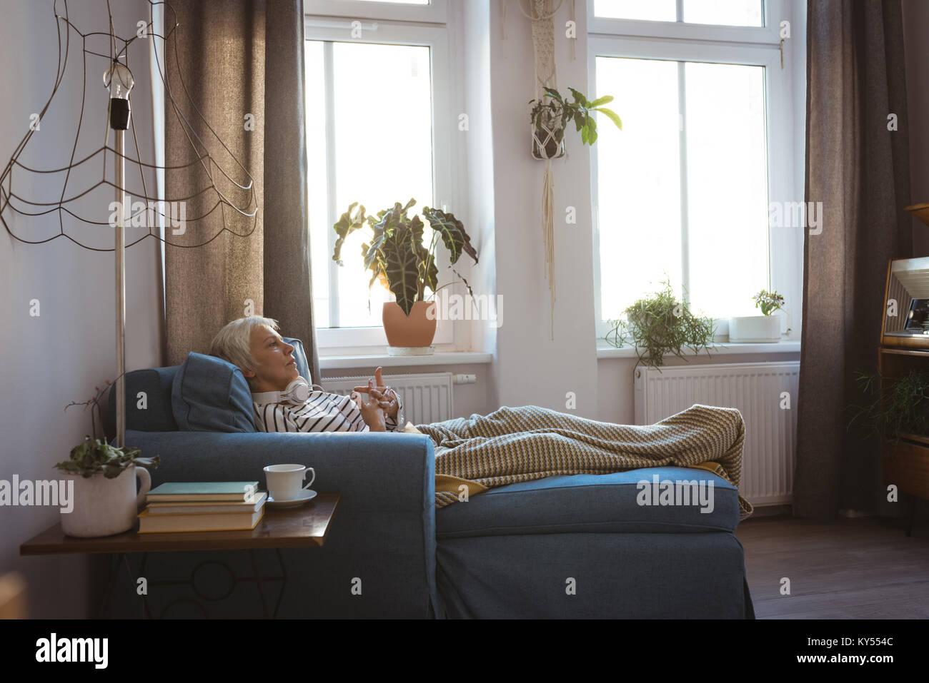 Senior donna rilassante sul divano nel soggiorno di casa Immagini Stock