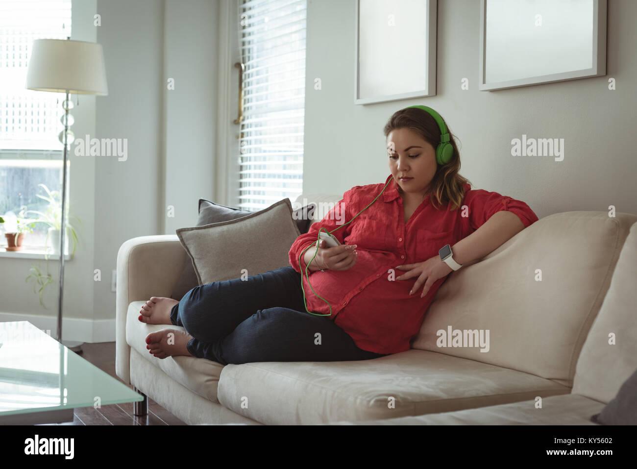 Giovane donna incinta seduta sul divano elenco musica sul suo telefono cellulare Immagini Stock