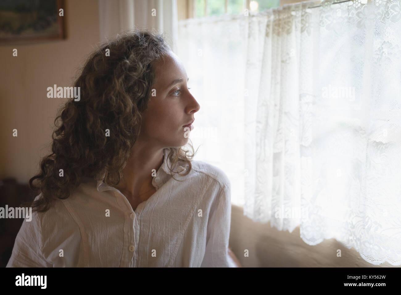 Donna che guarda attraverso la finestra nella stanza vivente Immagini Stock
