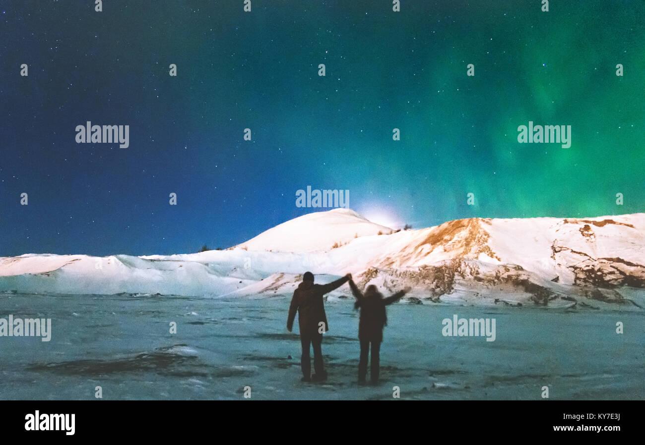 Accoppiare i viaggiatori godendo di Northern lights vista montagne sopra le mani alzate lo stile di vita di viaggio Immagini Stock