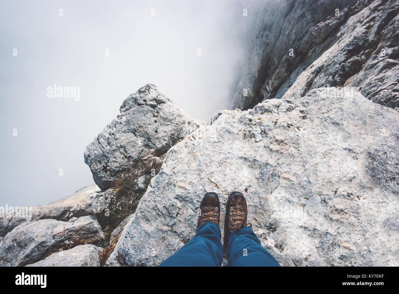Piedi di viaggiatori su scarponi da montagna rocciosa scogliera sopra le nubi velate stile di vita viaggio concetto Immagini Stock
