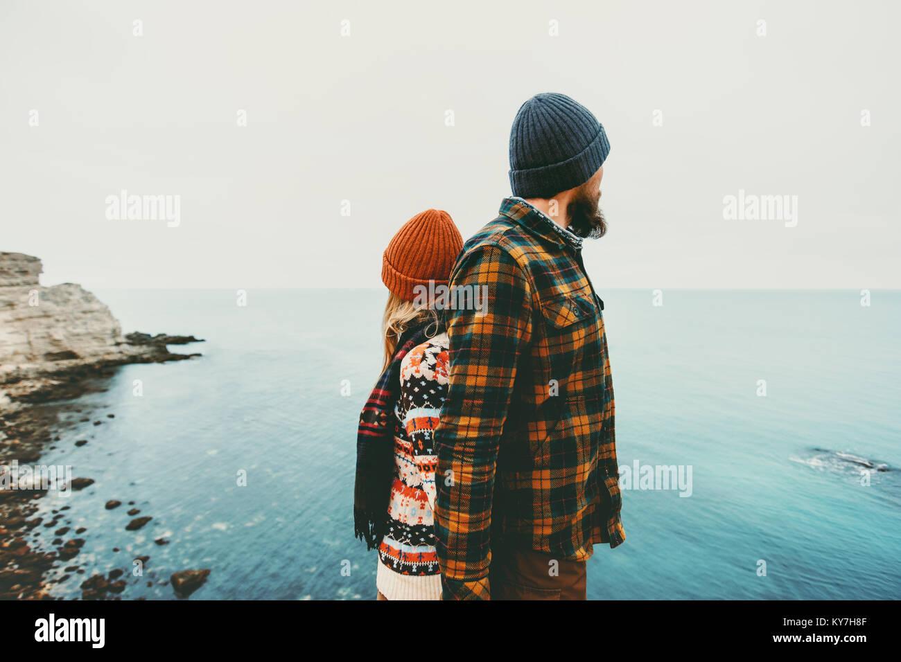 Gli amanti del giovane uomo e donna in piedi spalle insieme amore e viaggio felice emozioni concetto di stile di Foto Stock