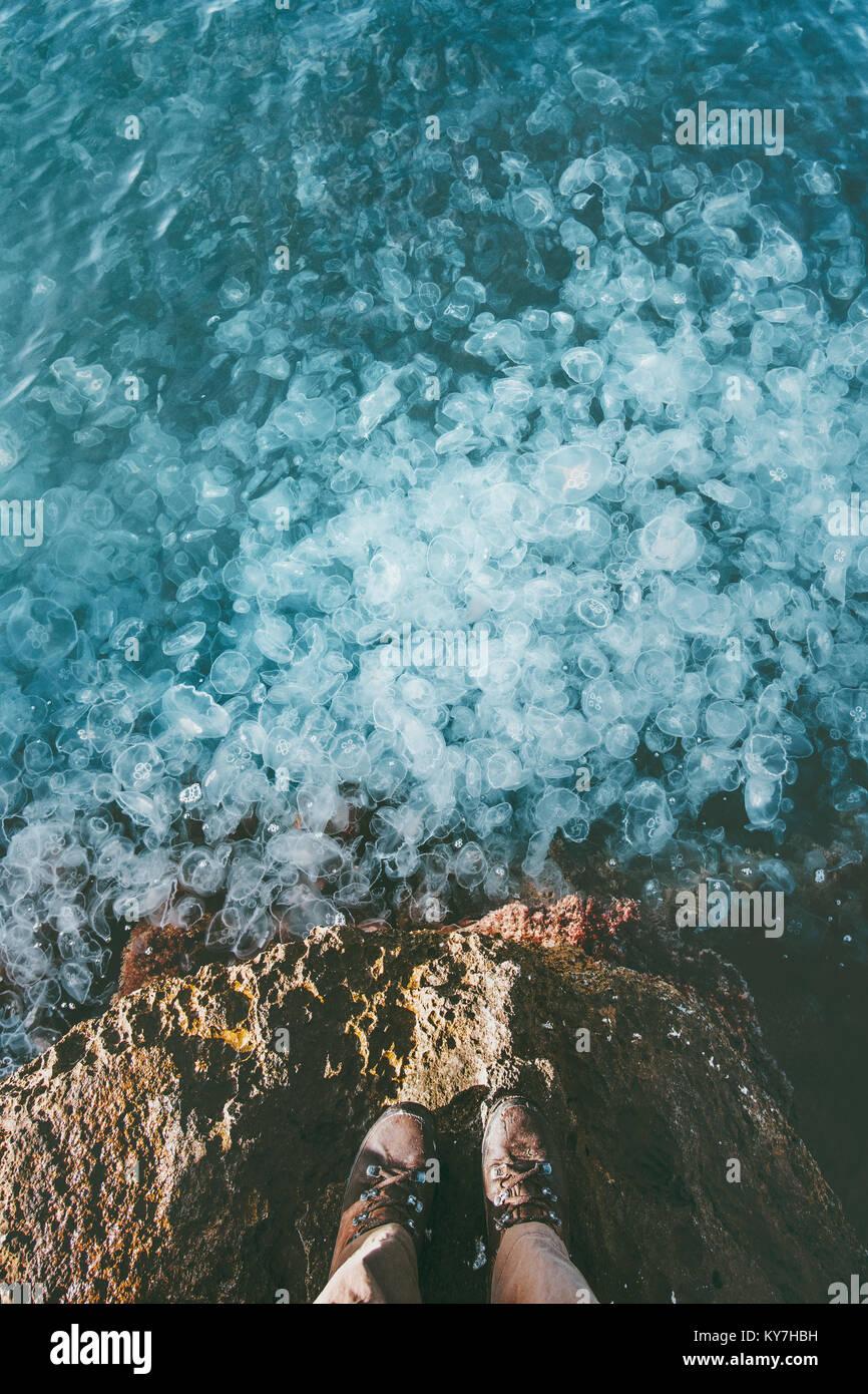 Piedi traveler stivali in piedi al di sopra del bordo mare pieno di meduse in acqua stile di vita viaggio avventura Immagini Stock