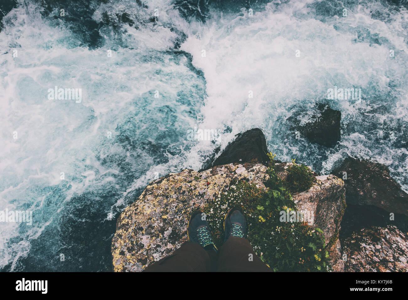 Piedi traveler permanente sulla pietra ad acqua di un fiume di viaggio il concetto di stile di vita Vacanze avventura Immagini Stock
