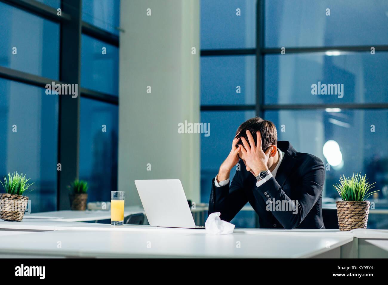 Sottolineato imprenditore avendo problemi e mal di testa sul posto di lavoro Immagini Stock