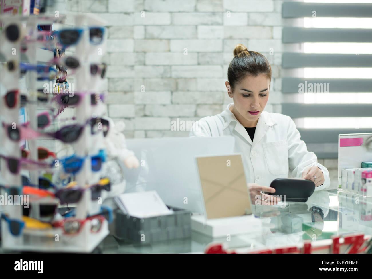 Giovane donna lavoratrice in farmacia cercando bicchieri box Immagini Stock