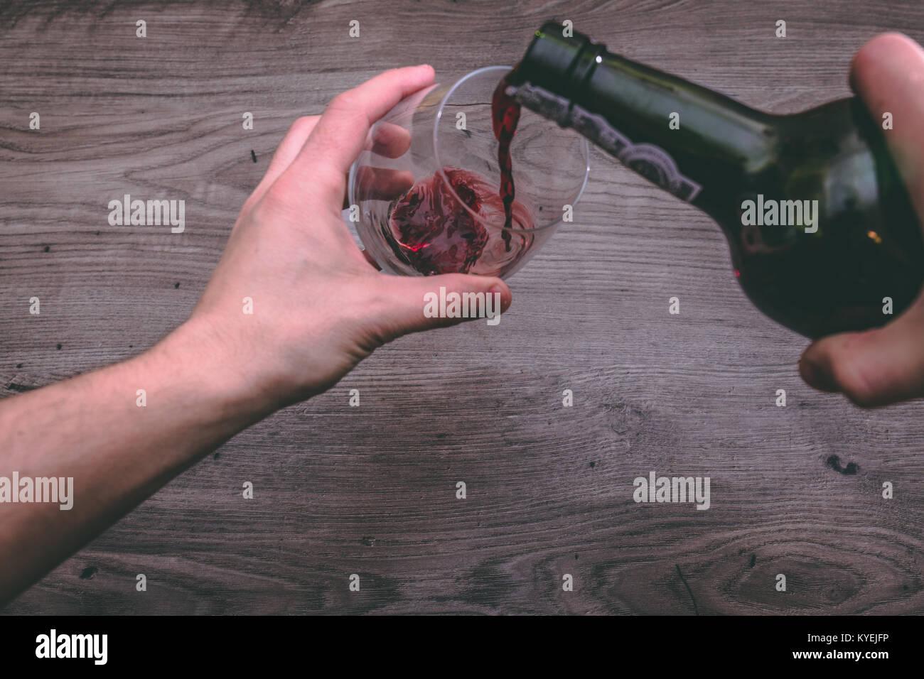 Vista dalla cima di una mano che tiene un vino rosso bottiglia e versarla in un bicchiere Immagini Stock
