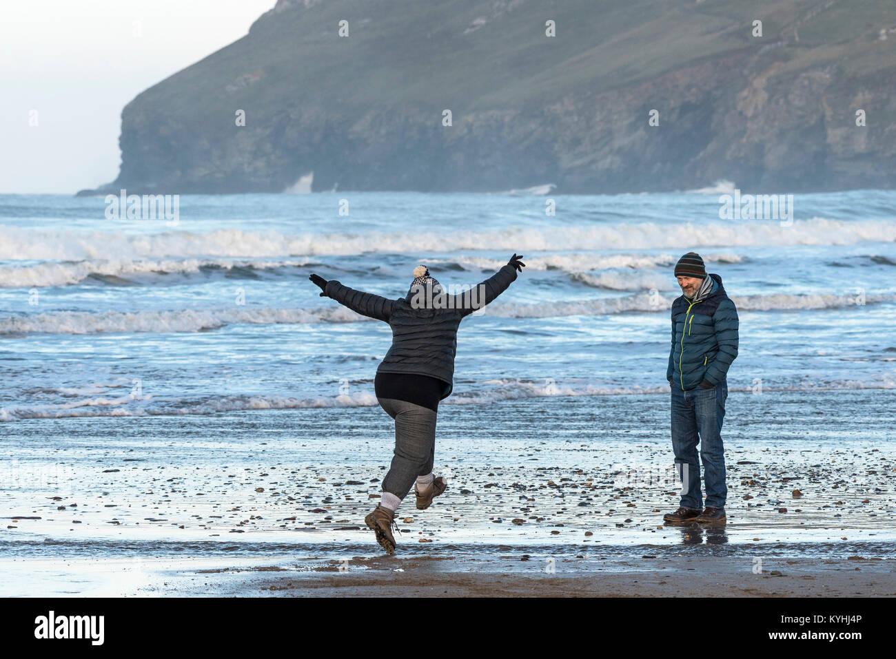 Polzeath - una donna salta sopra un piccolo flusso su Polzeath Beach a nord della costa della Cornovaglia. Immagini Stock