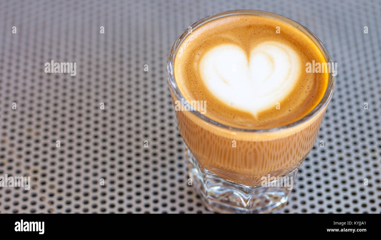 Vista superiore del cortado caffè in un bicchiere con la schiuma a forma di cuore Immagini Stock