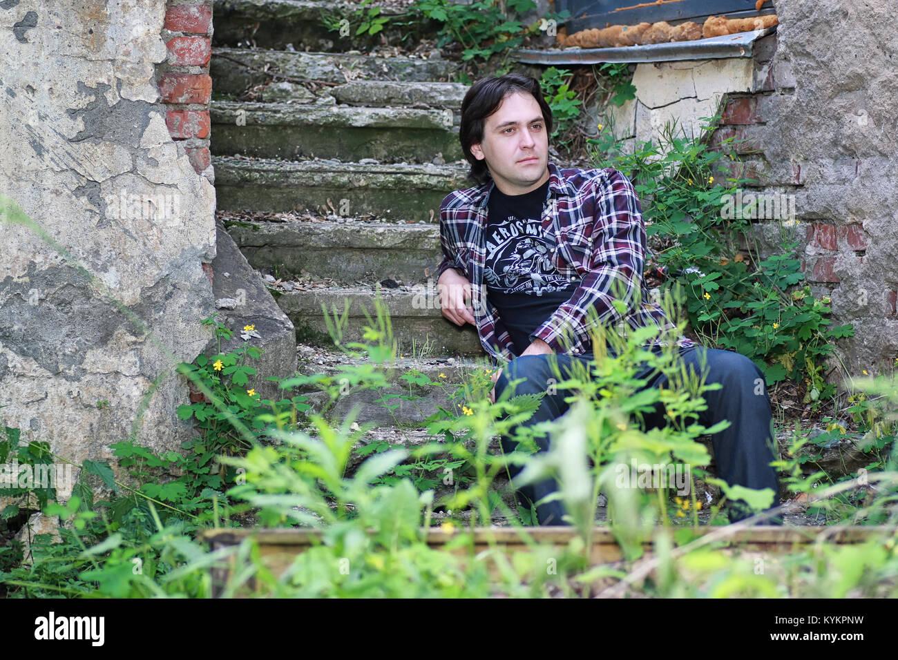 Uomo seduto sul gradino abbandonati Foto Stock