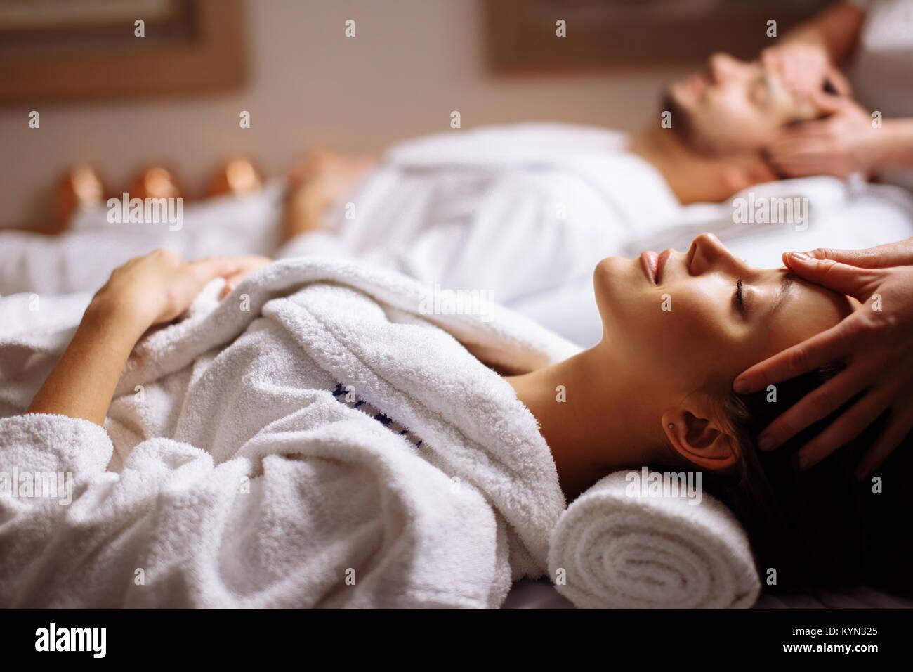 Felice giovane bella giovane godendo di massaggio della testa a spa Immagini Stock