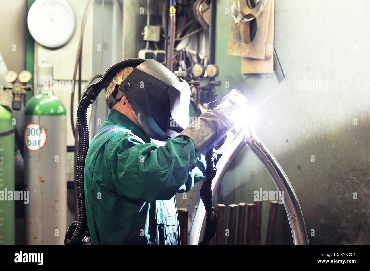 Saldatrice in una società industriale lavorando su un pezzo di lavoro Immagini Stock