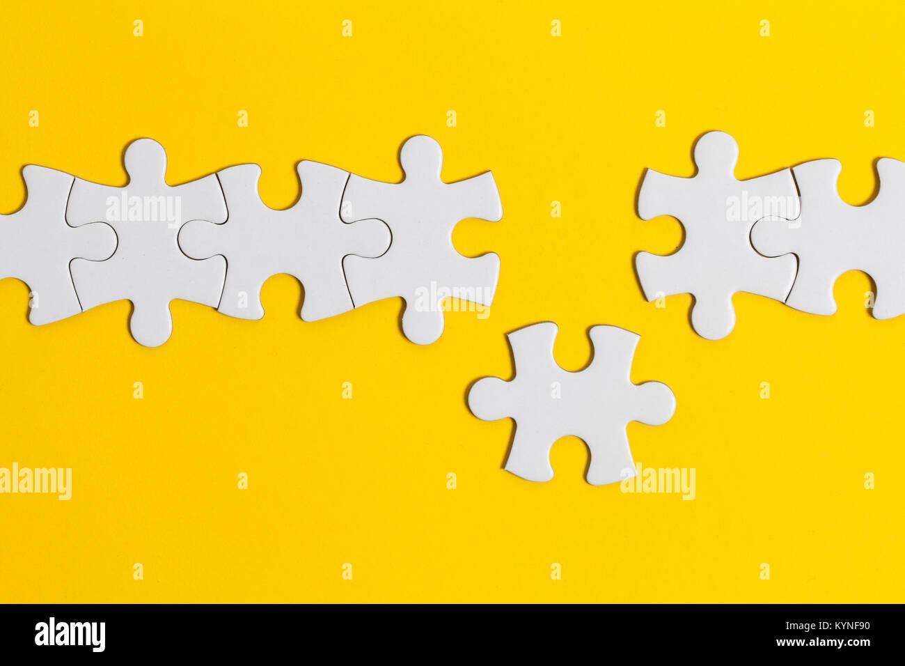 White jigsaw puzzle pezzi su uno sfondo giallo. Business del concetto di soluzione Immagini Stock