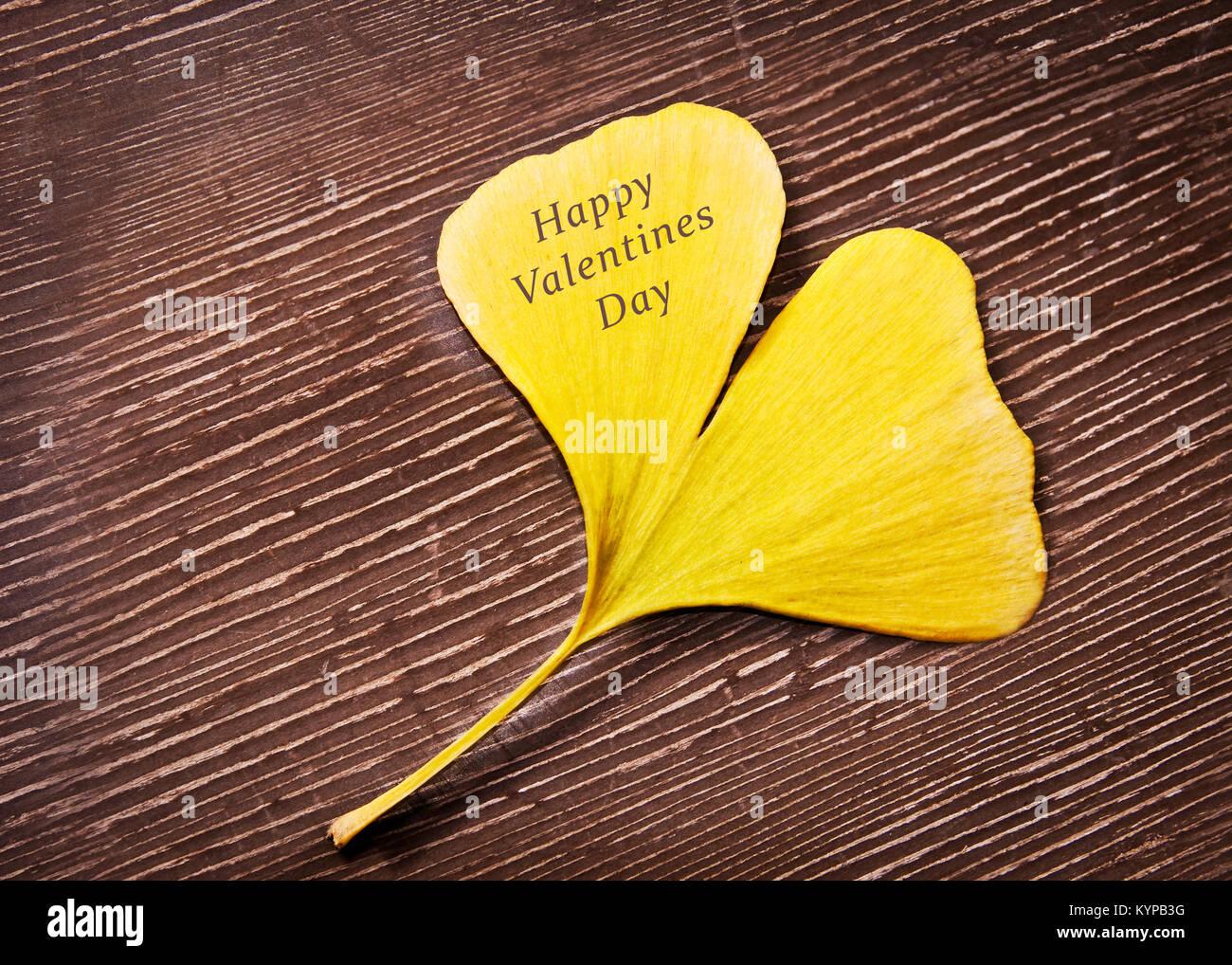 Felice il giorno di San Valentino scritto su un cuore giallo a forma di ginkgo biloba leaf Immagini Stock