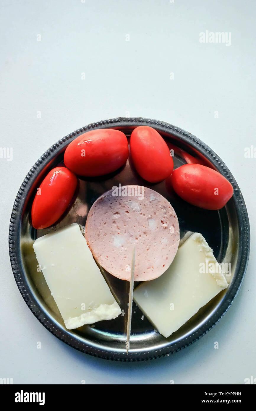Semplice Meze di formaggi graviera, salame all'aglio e pomodori Immagini Stock